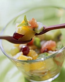 Exotic fruit salad in glass dish and on wooden spoons