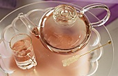 Tea in glass teapot and glass; crystal sugar