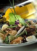 Salad with tuna, sardines & vegetables; white wine bottle