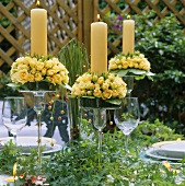 Yellow candles with roses in glass candlesticks on table