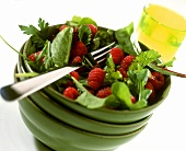 Herb salad with fresh raspberries in green bowl