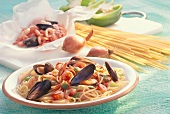 Spaghetti with seafood on plate in front of ingredients