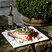 Leg of lamb with rosemary on stone wall, olive oil bottle