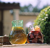 Sangria and iced tea in glass jugs on a stone wall