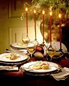 Weihnachtlich gedeckter Tisch mit Lachsgericht und Weisswein