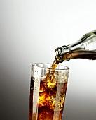 Cola aus Flasche in Glas mit Eiswürfeln gießen