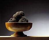 Black truffles in a brown ceramic bowl