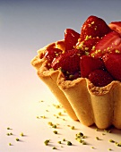 Tartlet with strawberries and chopped pistachios