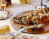 Yeast plait with poppy seeds and sugar on wooden plate