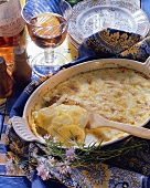 Potato gratin with wooden spoon in baking dish; rose wine