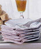 A pile of white plates with pink fabric napkins and forks