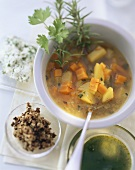 Vegetable soup with chopped olives, rosemary, herb mousse