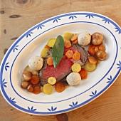 Beef fillet, breadcrumb dumplings & root vegetables on platter