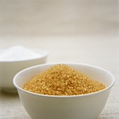 Brown sugar in white bowl in front of white sugar
