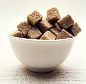 Brown sugar cubes in white bowl