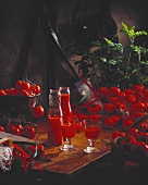 Tomato juice in bottles and glasses surrounded by tomatoes
