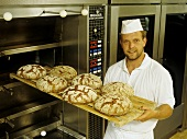 Baker with baked loaves at the oven