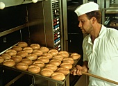 Baker taking a tray of rolls out of the oven