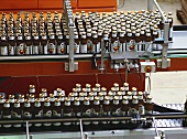 Fruit juice bottles on filling machine in drinks factory