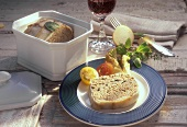 Goose liver pate in pate dish and on plate