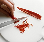 Cutting chili pepper into strips