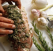 Rubbing rolled pork joint with herbs