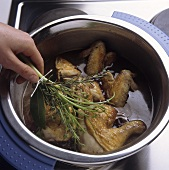 Putting a bunch of herbs on braised chicken pieces