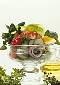 Vegetable salad with egg, lettuce & herbs in glass bowl