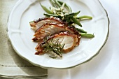 Suckling pig with green beans and rosemary on plate