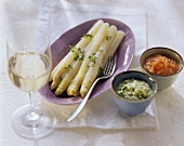White asparagus with two sauces and white wine glass