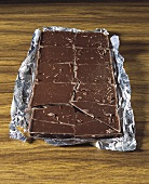 Chocolate bar, broken into pieces, on silver paper