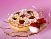 Small cherry cake with icing sugar on glass plate