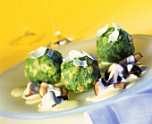 Spinach dumplings on mushrooms with cream sauce and parmesan