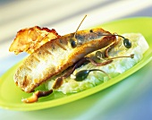 Sea bass with bacon and capers on lettuce