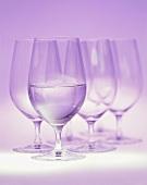 Mineralwasser im Glas vor einigen leeren Gläsern