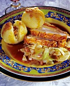 Roast pork on white cabbage with potato dumplings