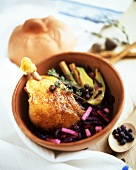 Duck leg on apple & red cabbage in brown bowl