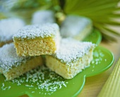 Coconut cake, cut into pieces, on green plate