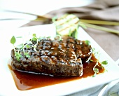 Glazed beef steaks with fresh herb leaves