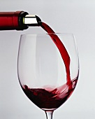 Pouring red wine from bottle with silver foil into a glass