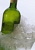 Half-full white wine bottle in ice bucket