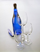 Empty wine glasses; sparkling wine bottle and waiter's knife