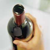 Hand holding red wine bottle ready to pour