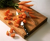 Carrots, partly sliced, with knife on chopping board