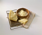 Pieces of Parmesan on grater and grated Parmesan in bowl