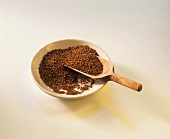 Linseed on a plate with wooden scoop
