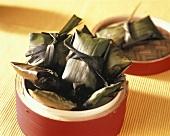 Gefüllte Bananenblätter im Bambusdämpfer