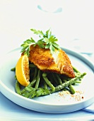 Breaded cod fillet on green beans with lemon slice