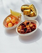 Three different tapas in white bowls