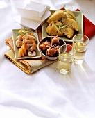 Assorted tapas in bowls on cloth; two sherry glasses